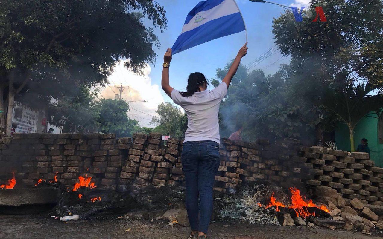 Kvinna i Nicaragua håller upp flagga